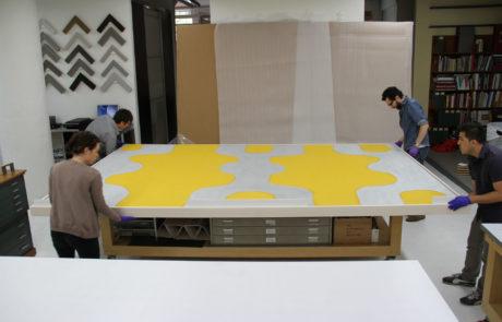 Staff Ensuring Artwork is Safely in Frame