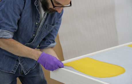 Staff Measures the Float Dimensions Between the Canvas and Frame