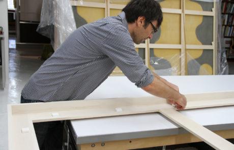 Staff Mounts Rag Board Spacers on Frame