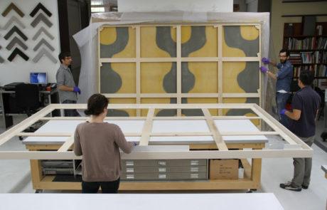 Staff Prepare to Move Artwork into Frame