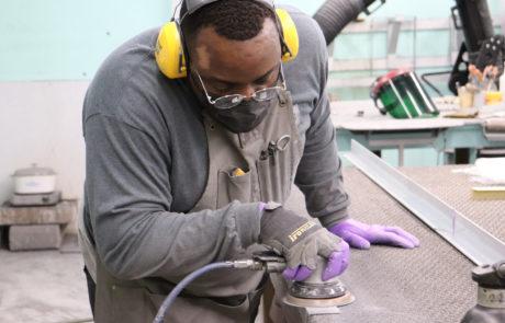 Nate sanding in metal shop.